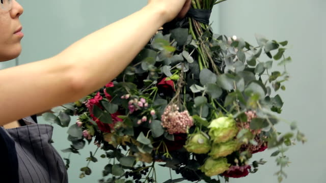 Flower arranger wraps a round bouquet around with a dark green ribbon video