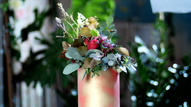 Flower bouquet in the rays of light, rotation, composition consists of Protea, Brunia green, Barbatus, Rose pion-shaped bordeaux, pistachio tree, Ornithogalum, eucalyptus, Santini video