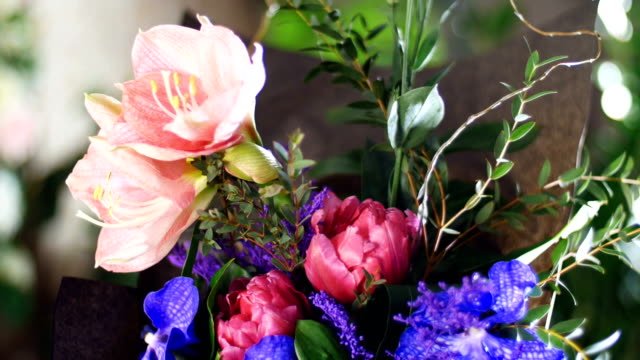 Flower bouquet in the rays of light, rotation, composition consists of Eustoma, eucalyptus, Amaryllis pink, Orchid vanda, Tulip piano, solidago. in the background a lot of greenery video