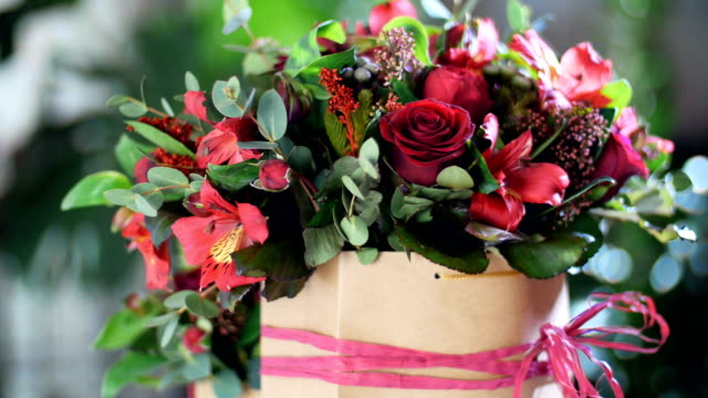 Flower bouquet in the rays of light, rotation, the floral composition consists of Alstroemeria, Rose prestige, Brunia green, solidago, eucalyptus, Rose pion-shaped bordeaux video
