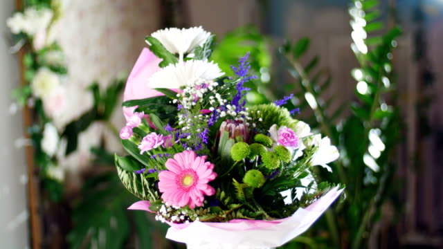 Flower bouquet in the rays of light, rotation, the floral composition consists of Chrysanthemum anastasis, gypsophila, solidago, Barbatus, Protea, Carnation, gerbera video