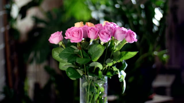 Flower bouquet in the rays of light, rotation, the floral composition consists of pink and orange Rose aqua. in the background a lot of greenery. Divine beauty video