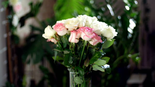 Flower bouquet in the rays of light, rotation, the floral composition consists white and pink Roses . Rose dzhemilja, Rose of avalanche .in the background a lot of greenery. Divine beauty video