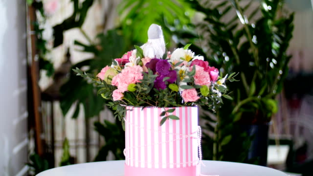 Flower bouquet in the rays of light, rotation, the floral composition consists of gerbera, Tulip piano, Santini , Alstroemeria, Rose odily, Orchid vanda, eucalyptus video