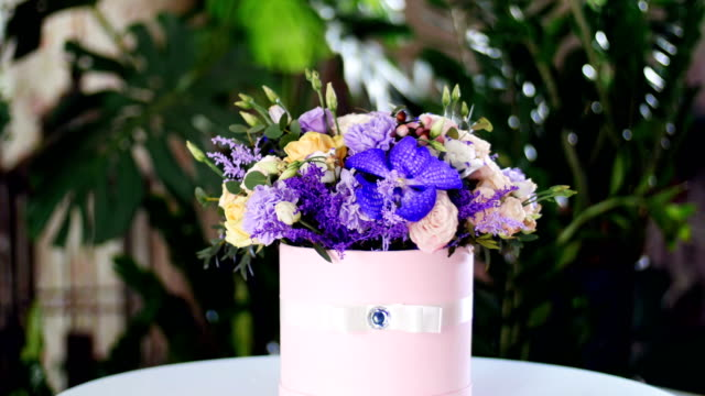 Flower bouquet in the rays of light, rotation, the floral composition consists of Orchid vanda, solidago, Carnation, Hiperikum, Rose pion-shaped, Eustoma, solidago, eucalyptus video