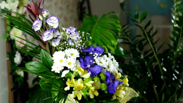 Flower bouquet in the rays of light, rotation, the floral composition consists of Alstroemeria, Chrysanthemum bacardi, Orchid vanda, Santini , gypsophila, Eustoma video
