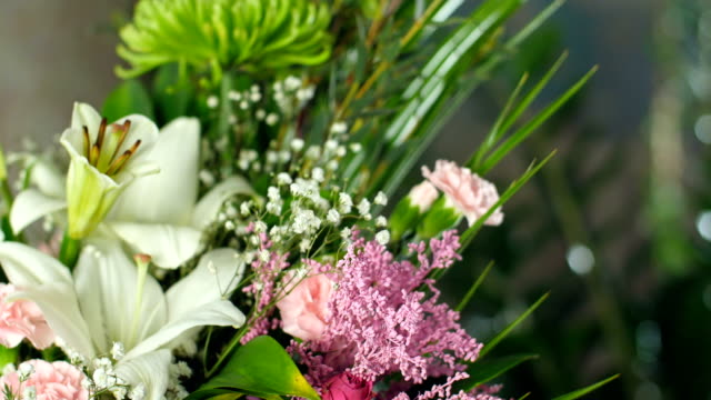 Flower bouquet in the rays of light, rotation, the floral composition consists of Phoenix robbeli, eucalyptus, Chrysanthemum, Rose lydia, Carnation, gypsophila, solidago, lily, Rose cappuccino, Eustoma video