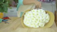 Flower shop, arranging flowers bouquet, florist wrapping paper around bouquet video