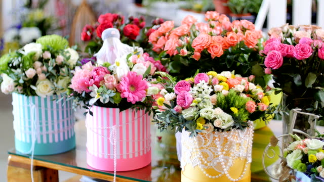 Flower shop, on the show-window, there are a lot of bouquets of flowers from pion-shaped roses, floral stylish compositions in colorful boxes with different flowers video
