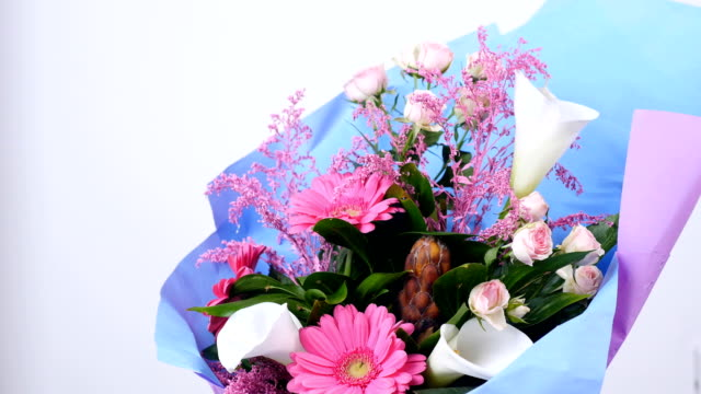Flowers, bouquet, rotation on white background, floral composition consists of pink gerbera, Protea, calla, Rose yana creamy, solidago Russus video