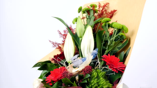 Flowers, bouquet, rotation on white background, floral composition consists of Santini , solidago, lily, gerbera, Barbatus, Russus video