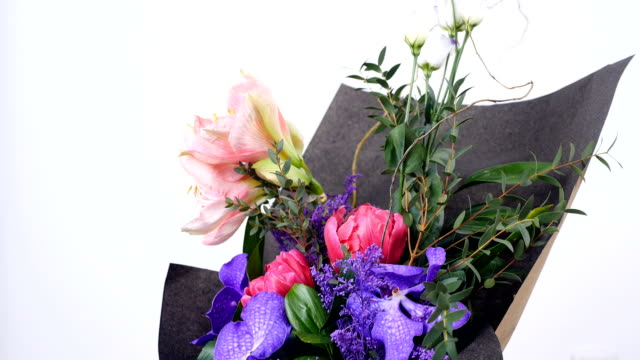Flowers, bouquet, rotation on white background, floral composition consists of Eustoma, eucalyptus, Amaryllis pink, Orchid vanda, Tulip piano, solidago video