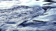 Flowing water in a blue river in slow motion video