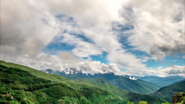 Fluffy, white cumulus clouds billow in the blue sky video