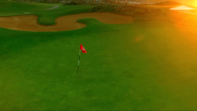 Fly around the golf pin on the sunset background video