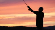 Fly Fishing Fisherman Silhouette on Lake at Sunset video