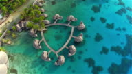 AERIAL: Flying above big luxury overwater bungalow villas along the jetty facing sparkling turquoise blue ocean lagoon and tropical white sandy beaches on sunny famous Bora Bora island in French Polynesia video