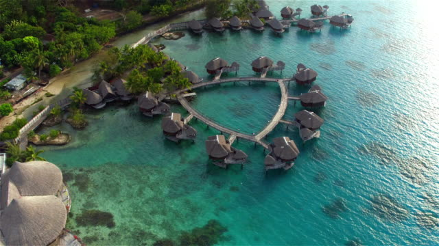 AERIAL: Flying above big luxury waterfront hotel on beautiful white sandy beach with deluxe overwater bungalows, fancy restaurants and outdoors swimming pool overlooking the perfect turquoise blue lagoon video