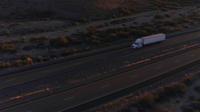 AERIAL: Flying above container semi truck transporting goods on busy highway video