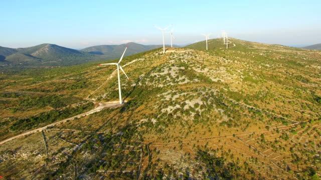 Flying above elegant ecological wind turbines on green hills video