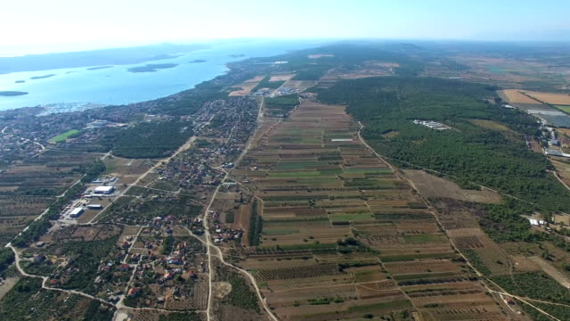 Flying above green fields and remote houses on dalmatian coast, Croatia video
