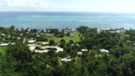 AERIAL: Flying above lush tropical island with small houses in local town under the lush exotic palm trees on the beach towards vast blue ocean and big beautiful reef in the background video