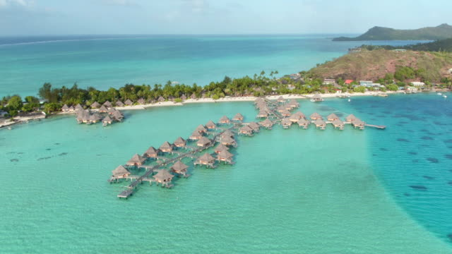 AERIAL: Flying above luxury overwater bungalows and exclusive beachfront villas in deluxe island hotel resort on secluded white sandy beach video
