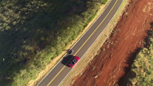 AERIAL CLOSE UP: Flying above red cabrio car driving along countryside road video