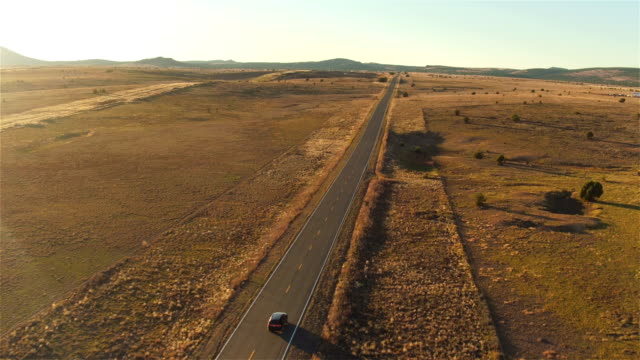 AERIAL: Flying above SUV car driving along empty countryside road at sunset video