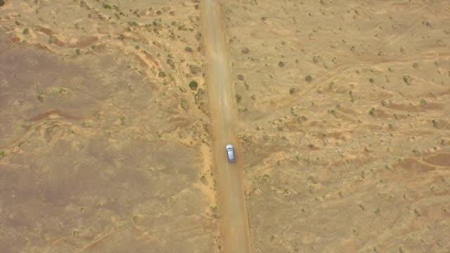 AERIAL: Flying above the car driving through huge sandy desert video