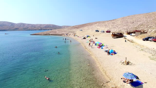 Flying above tourists on isolated beach of Pag island, Croatia video