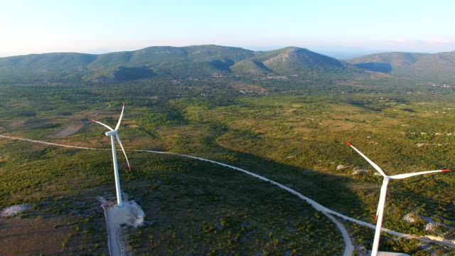 Flying above two elegant white wind turbines on green hills video