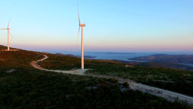Flying above two elegant white windmills on green hills video