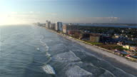 AERIAL: Flying along exotic sandy Miami Beach with tall skyscrapers in business district and beachfront buildings resort and hotels at beautiful sunny morning on summer day video