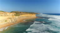 AERIAL: Flying along seashore cliff, above sandy beach and shallow emerald sea video