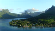 4K AERIAL: Flying around beautiful exotic island peninsula with tropical forest and blue lagoon and small local houses in local town video