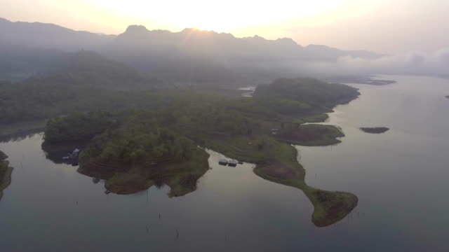 Flying around beautiful lake and silhouette mountain with fog in the morning, Aerial footage video