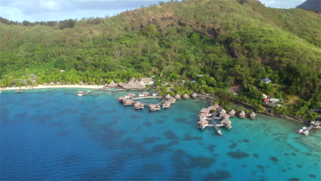 AERIAL: Flying around deluxe hotel resort on beautiful secluded white sandy beach on exotic island Bora Bora in stunning French Polynesia video