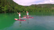 AERIAL: Flying around happy friends SUP boarding on beautiful lake video