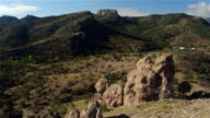 AERIAL: Flying around huge natural rock formation in mountain landscape video