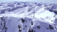 AERIAL: Flying around the cross on top of snowy mountain video