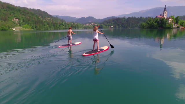 AERIAL: Flying around young couple SUP boarding towards lake island video