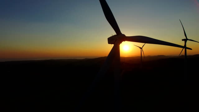 Flying close to windmill blades at dusk video