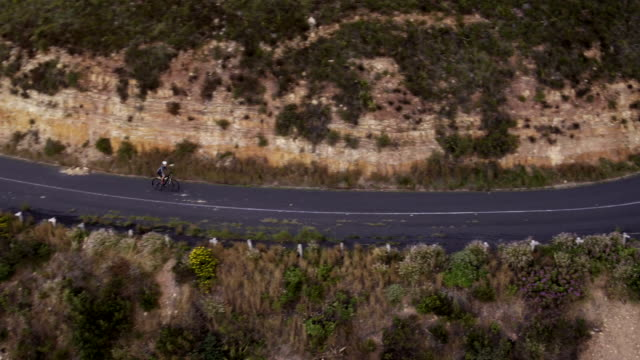 Flying drone shot of cyclist riding along mountain road video