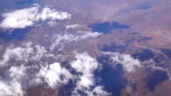 SLOW MOTION: Flying high above white clouds over the vast brown sand desert video