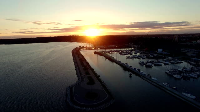 Flying low over water on marina lake at sunset video