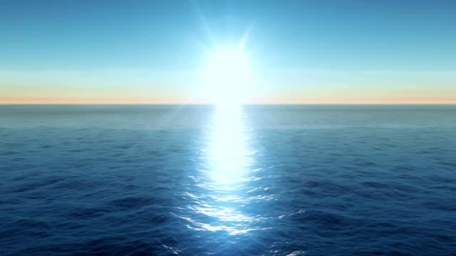 Flying over calm ocean blue sky and sun video