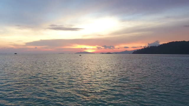 Flying over clean sea surface at sunset or sunrise. video