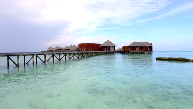 AERIAL: Flying over emerald ocean to the luxury overwater bungalows video