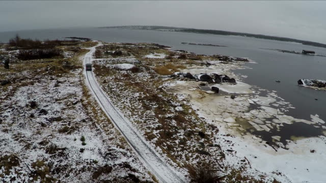 Flying over minivan driving on winter shore video